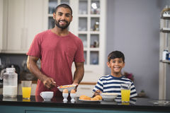 Portrait of happy father and his son having breakfast in kitchen Stock Images