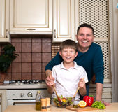 Portrait of happy father and his son preparing a salad in the kitchen Stock Images