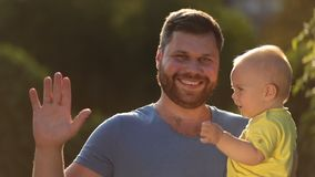Portrait of happy father and infant son outdoors stock footage
