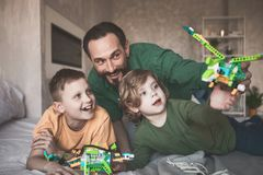 Cheerful dad having fun with sons. Portrait of happy father playing with satisfied kids while locating on bed in apartment. Happy family spending time together royalty free stock photo