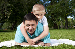 Portrait of happy father and son. The portrait of the father and the son, lay in park together, are happy Royalty Free Stock Image