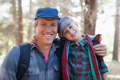Portrait of happy father and son with arm around. In forest Royalty Free Stock Photography