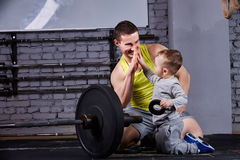 Portrait of happy father and son with barbell in the cross fit gym against brick wall. Stock Photos