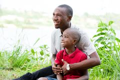 Portrait of Happy Father and Son In Park. Portrait of father with his son sitting in grass, having fun in the park in summer happy family. little boy playing stock image