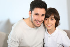 Portrait of happy father and son sitting on sofa. Portrait of father and son sitting in sofa royalty free stock images