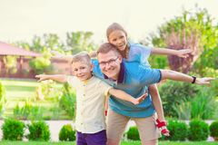 Portrait of happy father and two cute children playing at courty Stock Photos