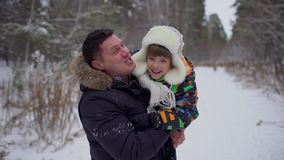 Portrait of happy father and a very cute happy little boy, his son in a snow winter park. smiling boy. Attractive family stock footage