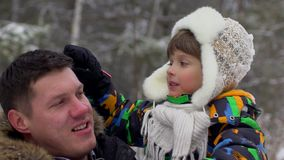 Portrait of happy father and a very cute happy little boy, his son in a snow winter park. smiling boy. Attractive family stock video