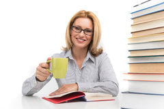 Portrait of happy female advocate sitting with books. Teacher at table with books drinking tea Stock Images