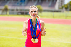 Portrait of happy female athlete with gold medals Stock Photos