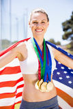 Portrait of happy female athlete holding up american flag with gold medal. In stadium Stock Photos