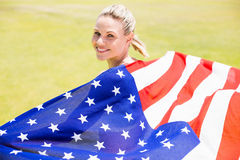 Portrait of happy female athlete holding up american flag with gold medal. In stadium Royalty Free Stock Photography