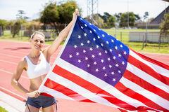 Portrait of happy female athlete holding up american flag. On running track Royalty Free Stock Photo
