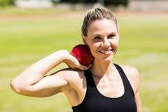 Portrait of happy female athlete preparing to throw shot put ball. In stadium Stock Image