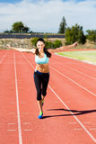 Portrait of happy female athlete running on running track Royalty Free Stock Images