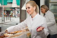 Portrait of happy female baker. With pastry smiling in bakery royalty free stock photography