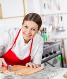 Portrait Of Happy Female Chef Cutting Ravioli Stock Images