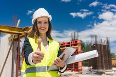 Portrait of a happy female construction foreman or architect sho. Wing thumbs up while holding a tablet and the plan of a building under construction Royalty Free Stock Images