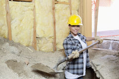 Portrait of a happy female contractor digging sand at construction site Royalty Free Stock Photos
