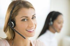 Portrait Of Happy Female Customer Service Representative. Close-up portrait of happy female customer service representative with colleague in background Stock Photography