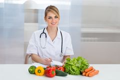Portrait of happy female dietician. With Fresh Vegetables And Diary royalty free stock images