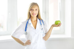 Portrait of a happy female doctor with green apple Royalty Free Stock Images