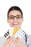 Portrait of happy female doctor holding pills Stock Images