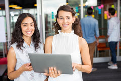Portrait of happy female executives using laptop. Male and female executives having discussion over laptop in office Royalty Free Stock Image