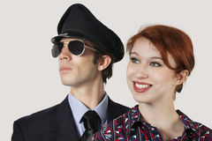Portrait of happy female flight attendant and pilot against gray background Royalty Free Stock Images