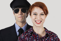 Portrait of happy female flight attendant and pilot against gray background Royalty Free Stock Image