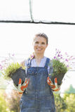 Portrait of happy female gardener holding potted plants at greenhouse Stock Image