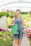 Portrait of happy female gardener holding watering can in greenhouse Royalty Free Stock Images