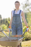 Portrait of happy female gardener pushing wheelbarrow at garden Royalty Free Stock Photography