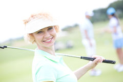 Portrait of happy female golfer holding golf club Royalty Free Stock Images