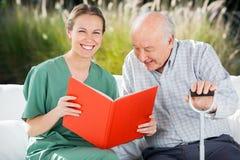 Portrait Of Happy Female Nurse Reading Book For. Senior men at nursing home stock photography