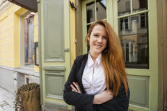 Portrait of happy female owner standing arms crossed outside restaurant Stock Image
