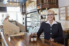 Portrait of a happy female owner standing at counter with spice jar in store Royalty Free Stock Images
