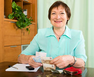 Portrait of happy female pensioner with cash and bills Stock Image