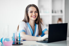 Portrait of happy female scientist working on laptop. In chemical laboratory Royalty Free Stock Image