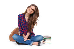 Portrait of happy female student sitting isolated. Stock Photography