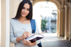 Portrait of a happy female student writing notes Stock Photos