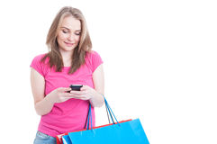 Portrait of happy female texting on cellphone while doing shoppi Royalty Free Stock Photography