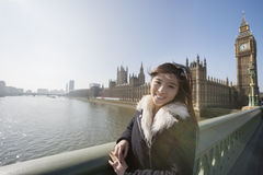 Portrait of happy female tourist visiting Big Ben at London, England, UK Royalty Free Stock Images
