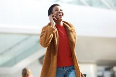 Happy female traveler walking and talking with mobile phone stock photo