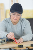 Portrait happy female woodworker drafting new project at workshop Stock Photography