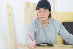 Portrait happy female woodworker drafting new project at workshop Royalty Free Stock Photo