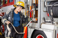 Portrait Of Happy Firefighter Adjusting Hose In. Portrait of happy female firefighter adjusting water hose in truck at fire station royalty free stock photos
