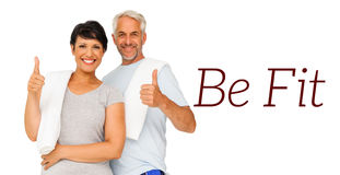 Portrait of a happy fit couple gesturing thumbs up. Over white background Stock Photos