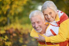 Portrait of happy fit senior couple in autumn park. Happy fit senior couple posing in autumn park stock images
