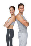 Portrait of a happy fit young couple with hands crossed Stock Photos